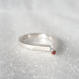 Sterling silver contemporary open ring with red garnet is placed on the white surface.