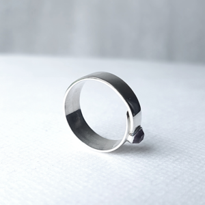 Overlap minimalist silver ring with amethyst stands on the white surface.