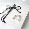 Contemporary silver gemstone ring is placed on the white gift box tied with black cotton string.