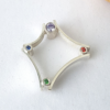 Contemporary silver ring with 8 cubic zirconias is placed on a white surface.
