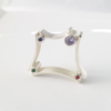 Minimalist silver ring with cubic zirconias stands on a white surface.