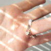 Asymmetrical Square Ring in Silver and Cubic Zirconia is worn on the forth finger.
