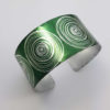 green cuff with silvery coloured scroll motif seen from above