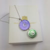 Purple and green disk pendant on top of box