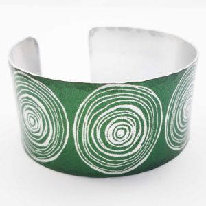 Front view of green women's suffrage bangle with large scroll motifs in a silvery colour
